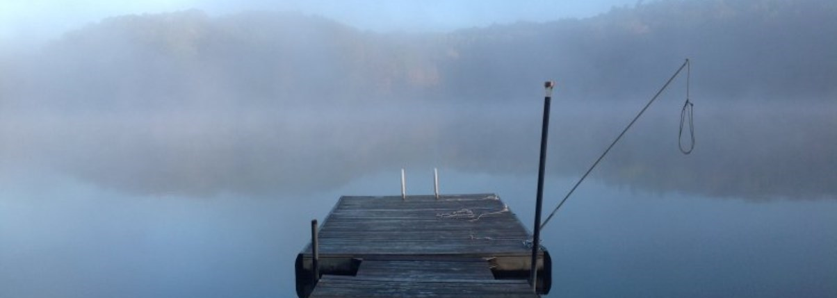 Floating dock on misty lake.